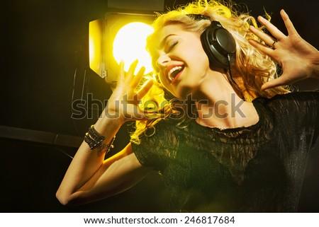 Attractive blonde beauty with headphones - stock photo