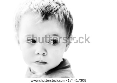 Attractive blonde boy looking out of the corner of his eye to the null space on the right side of the frame.  High key Black and White image. Room for copy space.  - stock photo