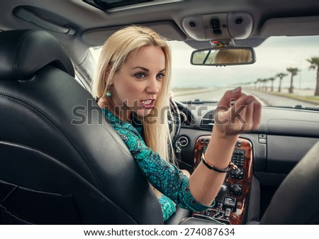 Attractive blonde female emotional talks to rear seat passenger - stock photo
