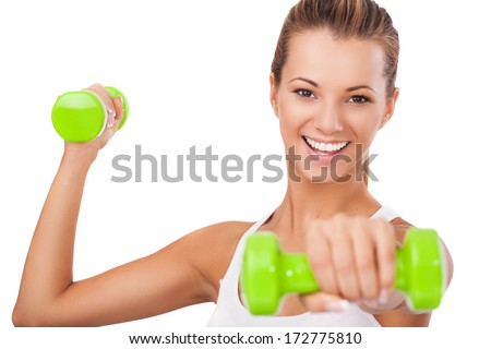 Attractive blonde female exercising with weights and smiling  - stock photo