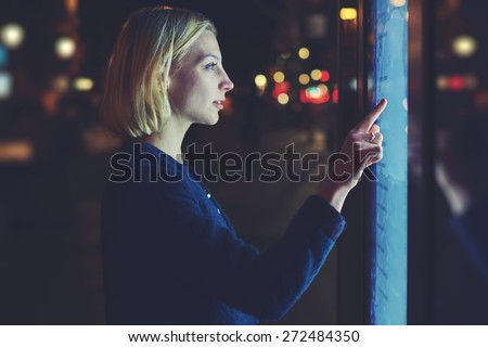 Attractive blonde female touching sensitive display with blue light while looking for touristic information with urban help technology system, futuristic device or smart bus station for self service - stock photo