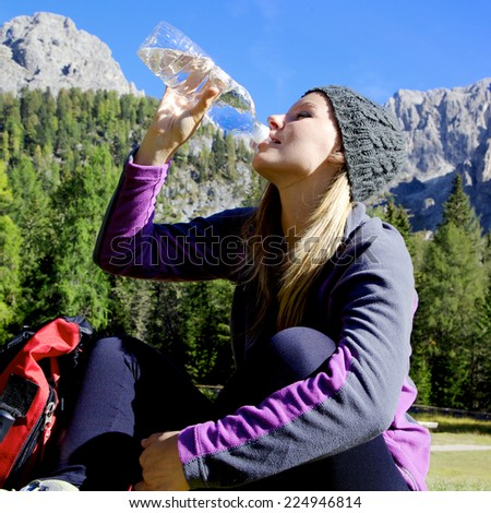 attractive blonde girl drinking water sitting on grass in front of mountain after a walk - stock photo