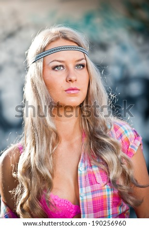 Attractive blonde girl posing fashion wearing a pink checked shirt outdoor. Young fair hair woman with flower power look and gorgeous eyes. Beautiful female with curly hair and pink bra. - stock photo