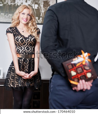 Attractive blonde girl smiling and waiting a surprise from her boyfriend. Man hiding behind a candies box of girlfriend. Man holding a box of chocolate at his back to make a gift to his girlfriend. - stock photo
