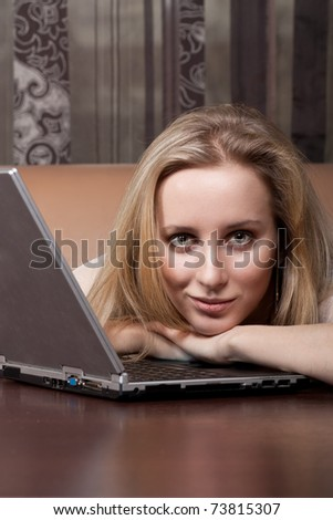 Attractive blonde girl with a laptop - stock photo