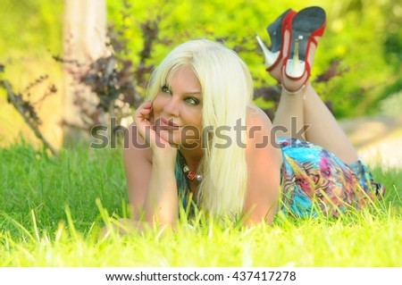 Attractive blonde girl with green eyes in green grass.Enjoy Nature.Magic eyes and magic smile. - stock photo