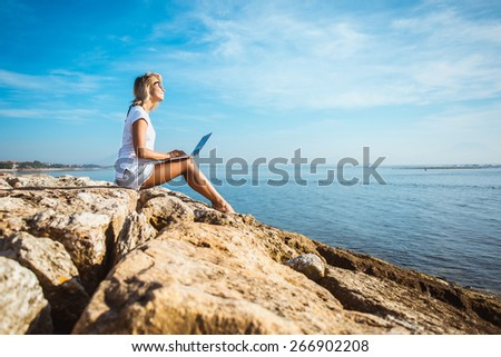 Attractive blonde hair woman working with a laptop on the seashore and look to the sea. Female freelancer working near the sea. - stock photo