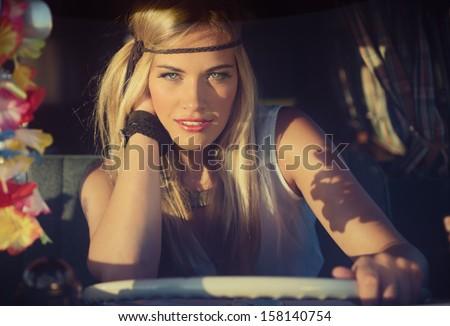 attractive blonde hippie girl in an old caravan - stock photo