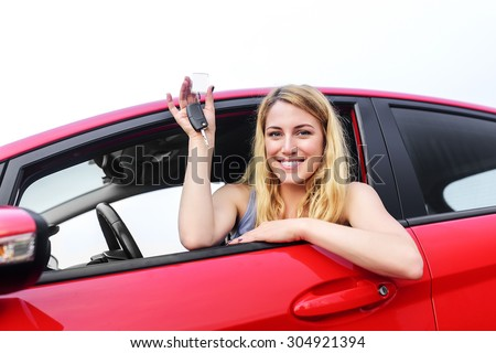 Attractive blonde in a car showing keys. - stock photo