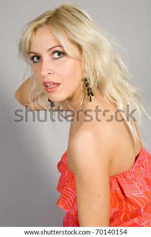 attractive blonde in a red dress on a gray background