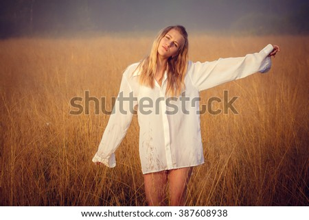 attractive blonde in a summer field at sunrise - stock photo
