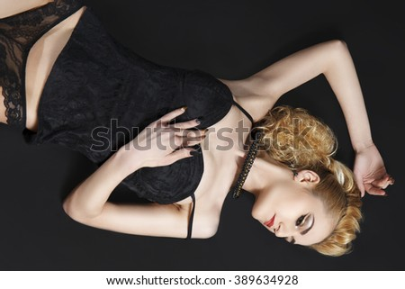 Attractive blonde model posing in black lace lingerie on ground in studio - stock photo