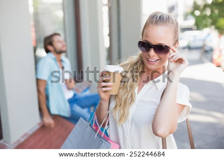 Attractive blonde on a shopping trip on a sunny day in the city - stock photo