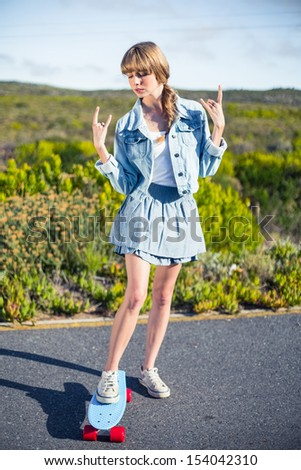 Attractive blonde on her skateboard making rock and roll hand gesture - stock photo