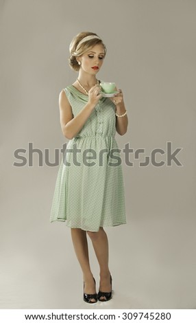 Attractive blonde retro fifties woman in green dress with black shoes holding mint green porcelain teacup and saucer - stock photo