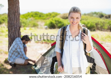 Attractive blonde smiling at camera while partner pitches tent on a sunny day - stock photo
