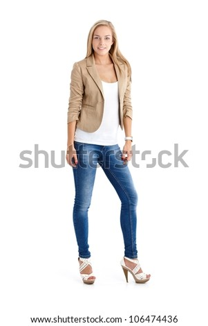 Attractive blonde teenager in trendy jeans and high heels, full length studio portrait.