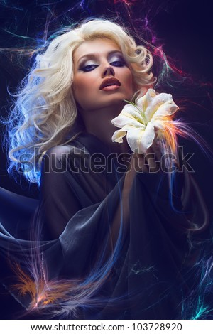 Attractive blonde with blue eyes holding white lily in hands on abstract lighting background