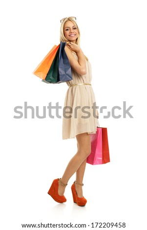 Attractive blonde with shopping bags in hand in elegant dress - stock photo