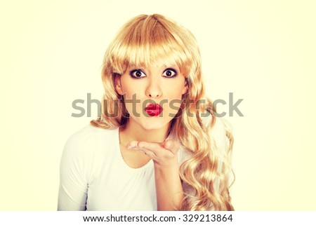 Attractive blonde woman blowing a kiss.