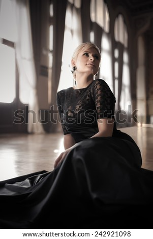 Attractive blonde woman dramatic portrait in big luxurious window hall.Beautiful film noir woman.Beautiful sexy woman in black lace elegant gown dress smiling.Sexy vamp femme fatale sensual lady. - stock photo