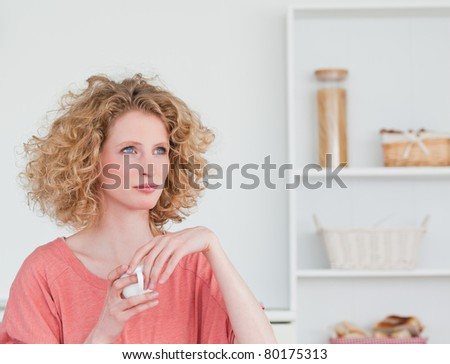 Attractive blonde woman drinking a cup of coffee while sitting in the kitchen in her apartment - stock photo