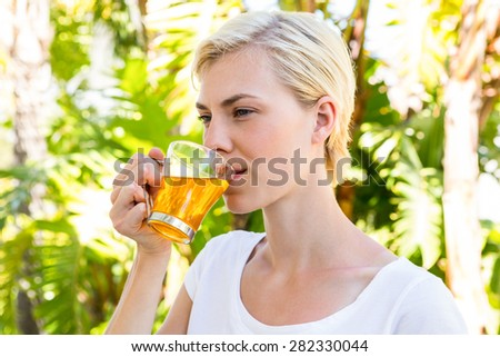 Attractive blonde woman drinking tea outside on a sunny day - stock photo