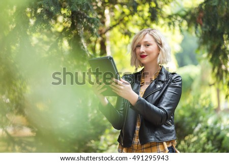 attractive blonde woman having a video call, using a tablet in the park.