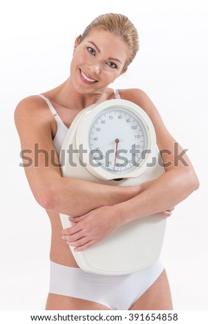 Attractive blonde woman  holding a scales and smiling