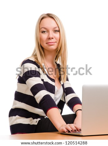 Attractive blonde woman in a striped black and white top sitting at her laptop isolated on white - stock photo