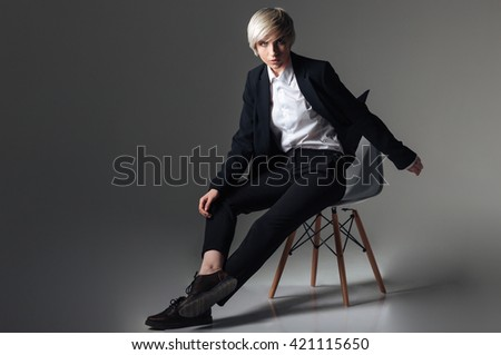 Attractive blonde woman in fashion cloth sitting on the chair over gray background and looking at camera - stock photo