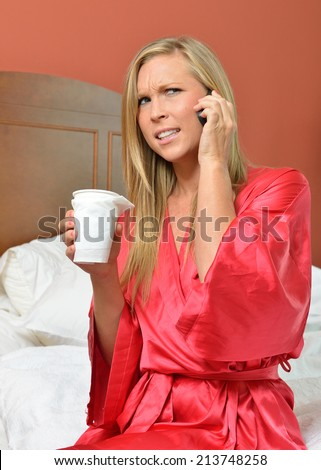 Attractive blonde woman in red silk robe holding a cup of coffee and talking on her smart phone while sitting on edge of bed - looks concerned or confused - stock photo