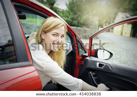 Attractive blonde woman in the car, opens the car door. - stock photo