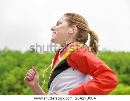 Attractive blonde woman jogging and listening to the player. Side view. - stock photo