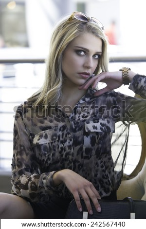 Attractive blonde woman seated on couch in urban setting, wearing animal print shirt with sun glasses on her head