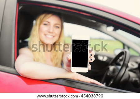 Attractive blonde woman showing smartphone out the window of a car. Focus on phone. - stock photo