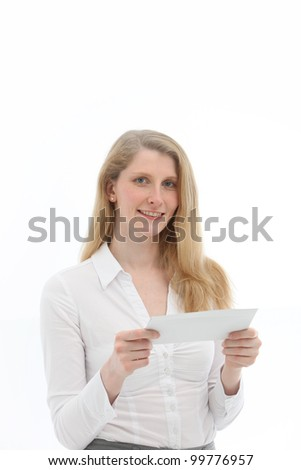 Attractive blonde woman smiling in anticipation at the thought of reading a letter which she is holding in her hands isolated on white
