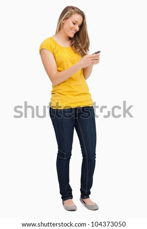 Attractive blonde woman smiling while using her cellphone against white background - stock photo