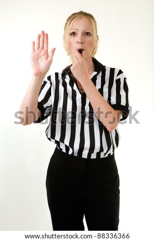 Attractive blonde woman wearing black and white striped referee uniform blowing on a whistle making a hand signal