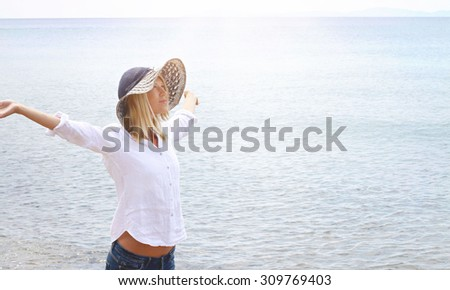 Attractive blonde woman wearing white shirt and straw hat breathing Happy With Raised Arms. Freedom concept. Hazy light image