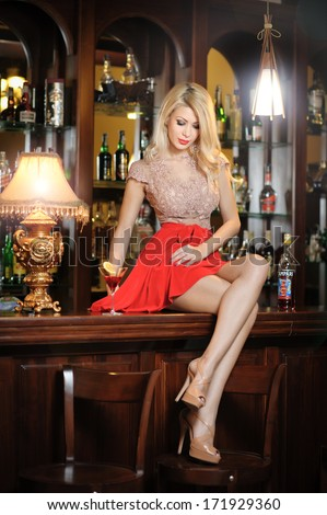 Attractive blonde woman with long hair in elegant nude and red dress sitting on bar stool. Gorgeous blonde model showing her long legs with high heels posing provocatively in vintage bar - stock photo