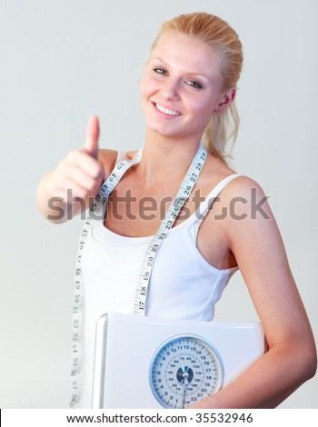 Attractive blonde woman with thumb up holding a scales and smiling at the camera with focus on woman - stock photo