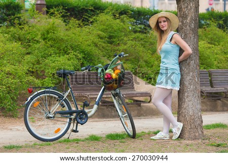 Attractive blonde womanwith straw hat standing in the park and posing next to bike with basket full of groceries. - stock photo