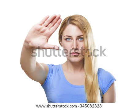 Attractive blonde women with a determined expression calling a halt with her hand holding it at arm's length. Isolated on white. - stock photo
