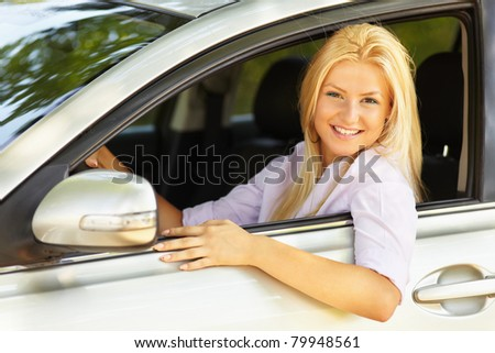 Attractive blonde young woman at the wheel in her new car
