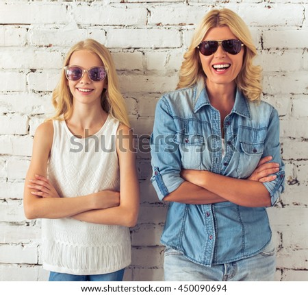 Attractive blondes, teenage girl and her mother, in sun glasses are looking at camera and smiling, standing with crossed arms against white brick wall - stock photo