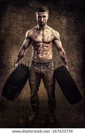 Attractive body builder with two car tires in his hands - stock photo