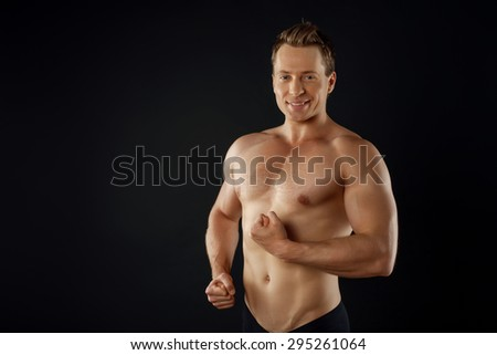 Attractive bodybuilder is straining muscles of arms and showing his perfect body. He is smiling and looking at camera confidently. Isolated on black background and there is copy space in left side - stock photo