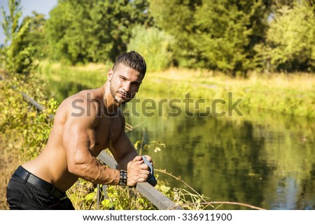 Attractive bodybuilder shirtless outdoor showing torso muscles, abs, pecs and arms, looking at camera - stock photo