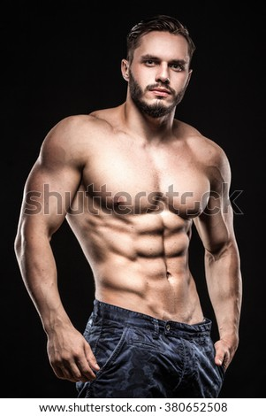attractive bodybuilder sportsman shows perfect body muscles on black background; fitness man; bodybuilding and gym sport; athlete guy; - stock photo
